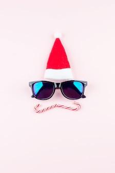 Fondo de navidad. imagen improvisada de santa de un sombrero y gafas en rosa.