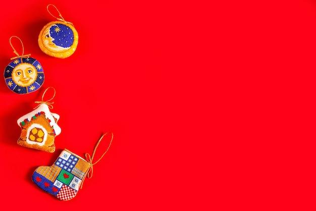 Fondo de navidad con juguetes de navidad bordados sobre fondo rojo.