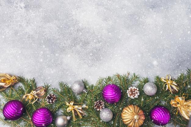 Fondo de navidad, juguetes y ramas de abeto en gris