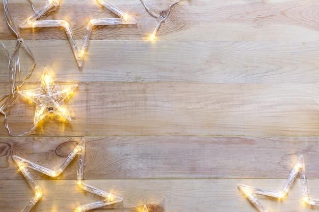 Fondo de navidad de madera con luces en forma de estrella.
