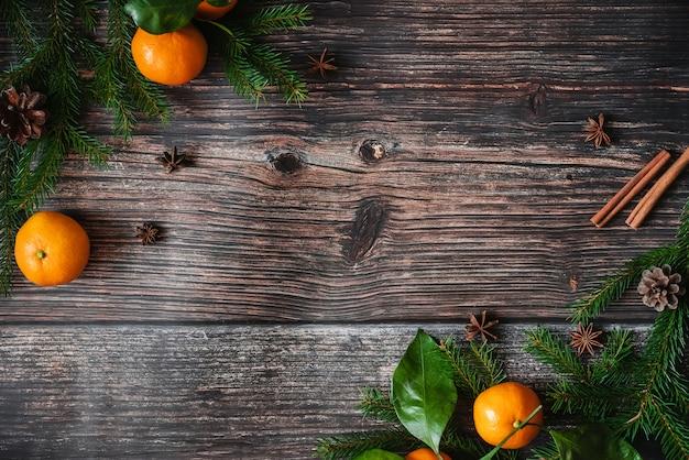 Fondo de navidad con mandarinas, ramas de abeto, canela y anís estrellado. marco decorativo festivo de invierno