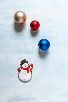 Fondo de navidad con un muñeco de nieve y bolas de navidad