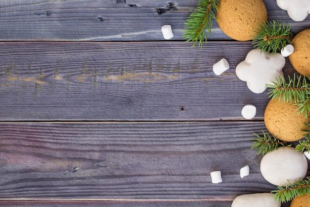 Fondo de navidad con pan de jengibre, malvavisco y rama de abeto