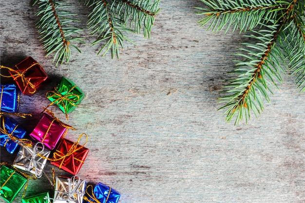 Fondo de navidad con pequeños regalos y una rama