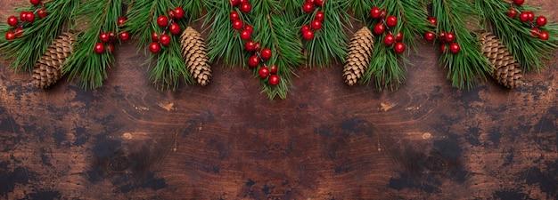 Fondo de navidad con ramas de abeto y acebo. vista desde arriba. banner horizontal copyspace