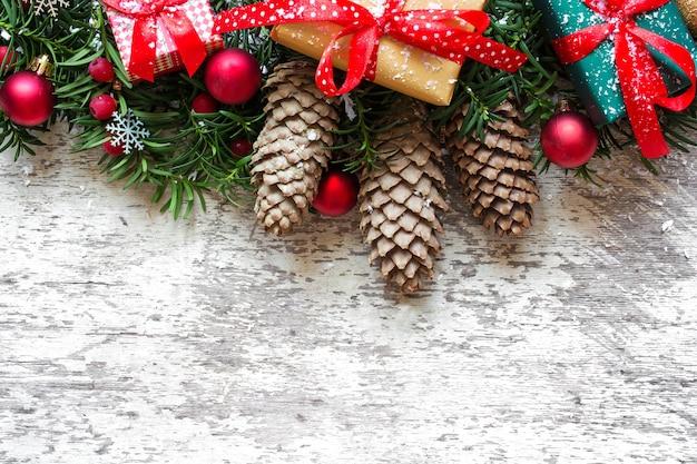 Fondo de navidad con ramas de abeto, adornos y cajas de regalo en tablero de madera blanca
