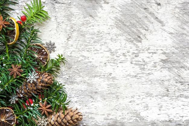 Fondo de navidad con ramas de abeto, adornos de comida, piñas