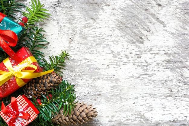 Fondo de navidad con ramas de abeto, adornos, piñas y cajas de regalo