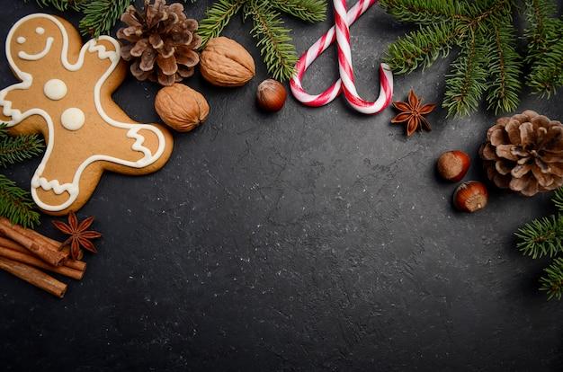 Fondo de navidad con ramas de abeto, conos, especias y pan de jengibre.