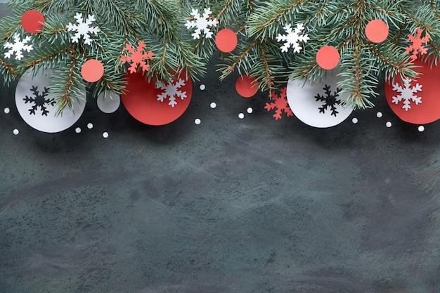 Fondo de navidad con ramas de abeto, decoraciones de papel rojo y blanco