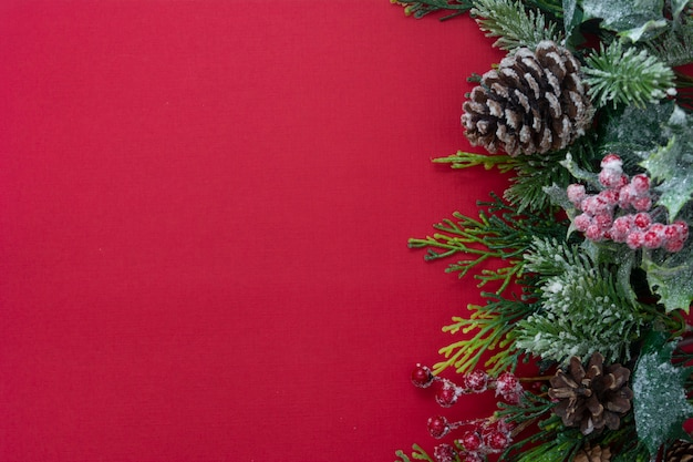 Fondo de navidad rojo con ramas de abeto, conos de pino. copia espacio