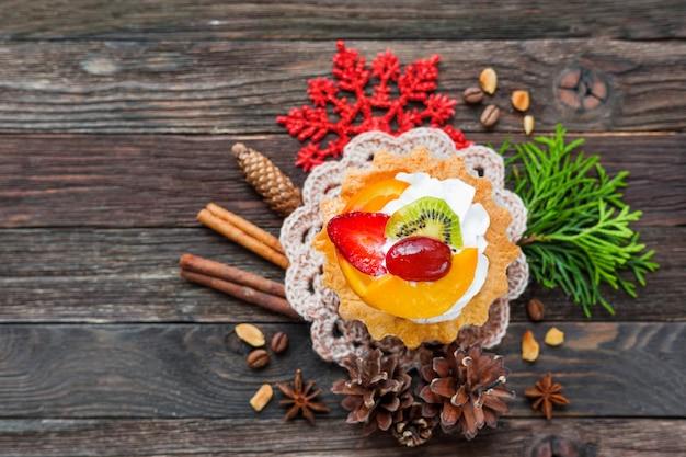 Fondo de navidad con tarta de frutas y decoraciones