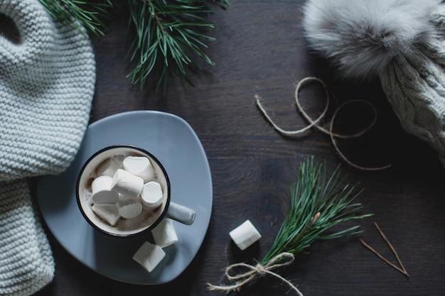 Fondo de navidad. una taza de café con malvaviscos, una bufanda tejida y una gorra, un color gris, ramitas de un árbol de navidad, vista desde arriba