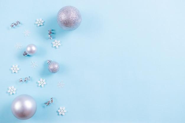 Fondo de navidad vista superior de la bola de navidad con copos de nieve en pastel azul claro