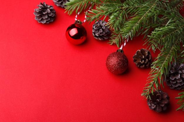 Un fondo navideño. ramitas de árbol de navidad, bolas de navidad y conos sobre un fondo rojo.