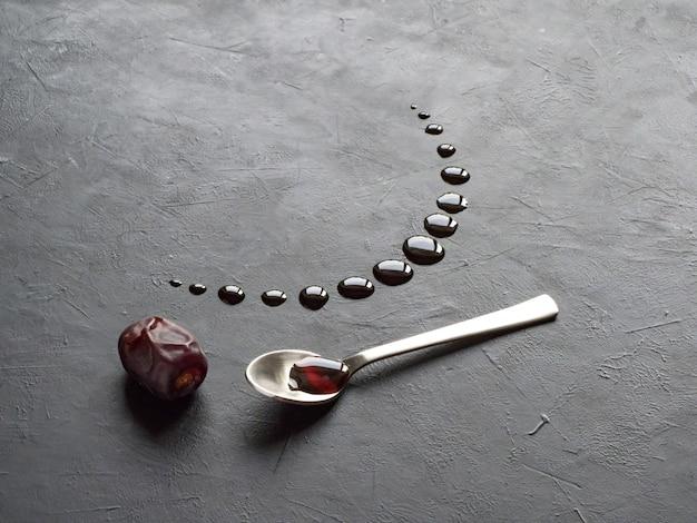 Fondo negro de ramadán con fechas y jarabe de fechas vertido en forma de luna creciente.