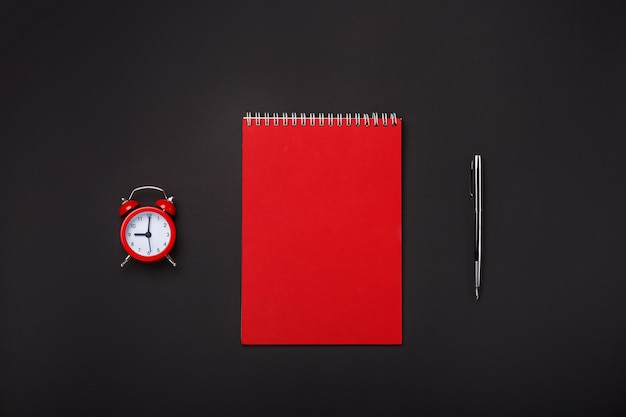 Fondo negro rojo alarma reloj libreta bolígrafo espacio en blanco escritorio