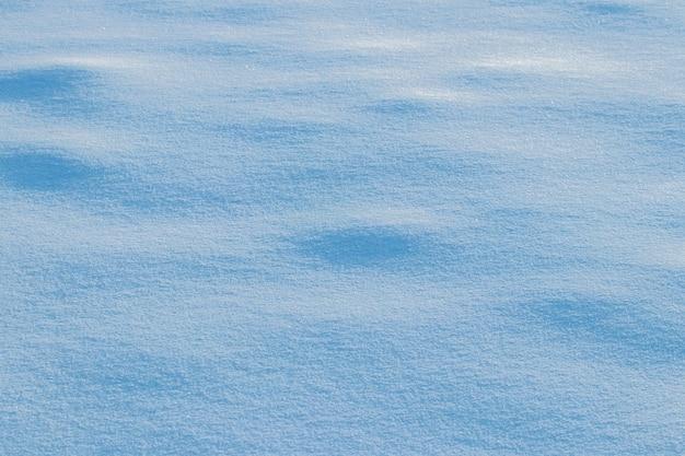 Fondo nevado, superficie nevada con una textura claramente expresada de nieve en el sol de la mañana