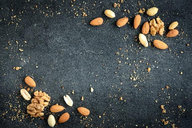 Fondo de nueces de almendras, cacahuetes y nueces con migas sobre fondo negro.