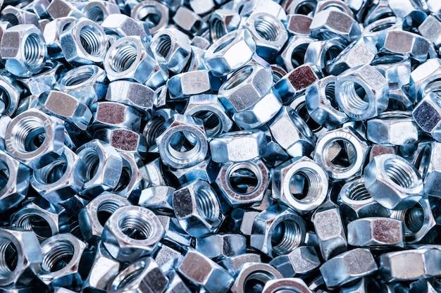 Fondo de nueces brillantes de primer plano. tornillos o sujetadores inoxidables nuevos. concepto abstracto industrial