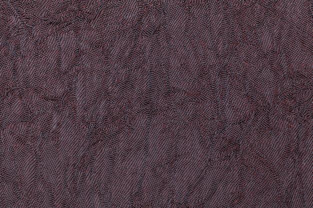Fondo ondulado púrpura oscuro de un material textil. tela con textura natural de cerca.
