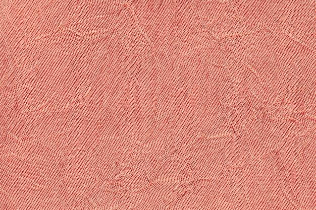 Fondo ondulado rojo claro de un material textil. tela con textura de pliegue de cerca.
