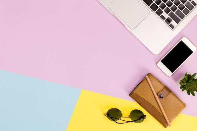 Fondo del ordenador portátil, lugar de trabajo moderno con el espacio del ordenador portátil, del smartphone y de la copia en fondo del color.
