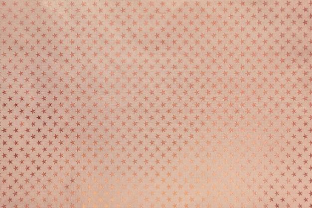 Fondo de oro rosa de papel de aluminio con un patrón de estrellas