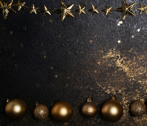 Fondo oscuro con adornos navideños dorados y estrellas, un lugar para texto o saludos de año nuevo