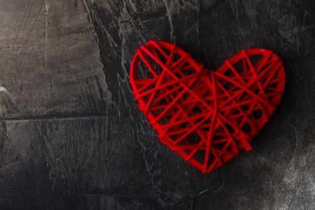 Fondo oscuro del día de san valentín con un corazón rojo.