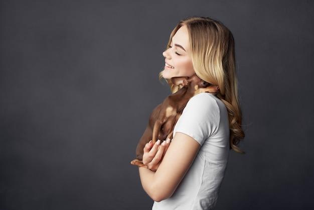 Fondo oscuro de estilo de vida de moda de perro de pedigrí de mujer hermosa