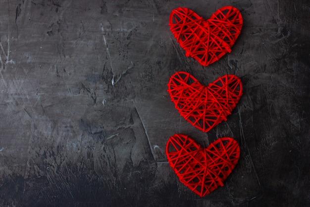 Fondo oscuro de san valentín con corazones rojos.