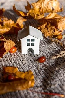 Fondo otoñal. casa de juguete y hojas de arce de otoño naranja secas en suéter de punto gris