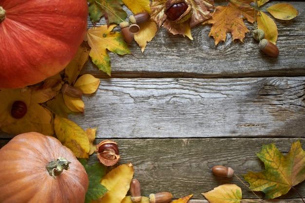 Fondo de otoño de acción de gracias en una superficie de madera oscura, calabazas, hojas marchitas, bellotas y castañas