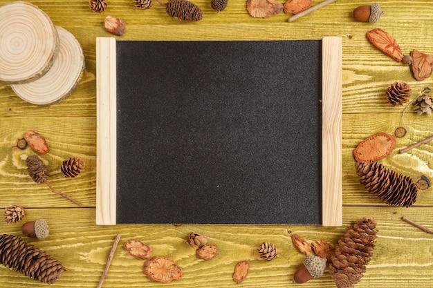 Fondo de otoño aplanada pedazos de madera, conos, bellotas y un tablero con espacio para texto sobre un fondo de madera verde grunge