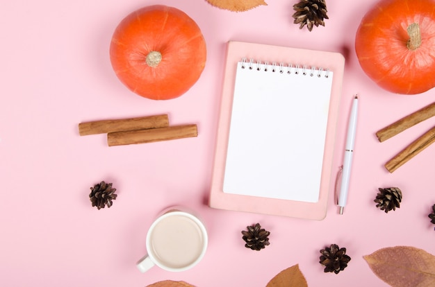 Fondo de otoño con bloc de notas, calabaza naranja, canela y hojas sobre fondo rosa