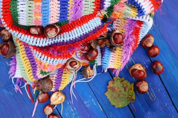 Fondo de otoño. castañas de indias en crochet a cuadros a rayas cálidas brillantes sobre tablas de madera azul.