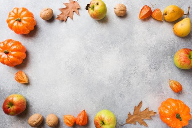 Fondo de otoño con hojas amarillas, calabazas, manzanas, peras y nueces