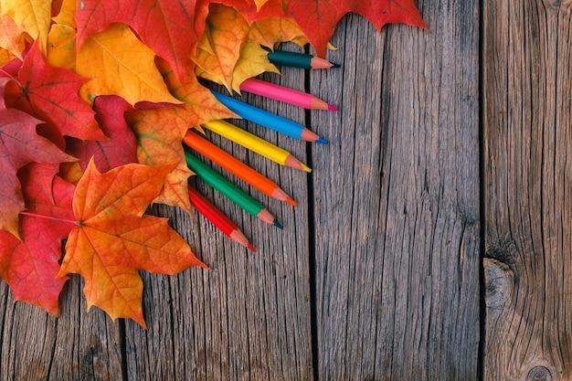 Fondo de otoño con hojas de arce en mesa de madera