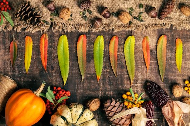 Fondo de otoño - hojas caídas y comida sana en la mesa de madera vieja