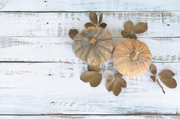 Fondo de otoño de hojas caídas y frutas de calabazas en mesa de madera.