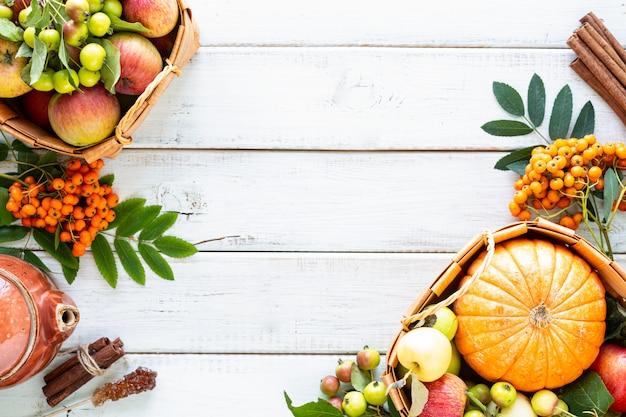 Fondo de otoño. manzanas, calabaza, manzanas del paraíso, serbal sobre madera blanca.