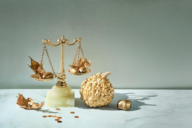 Fondo de otoño minimalista con escalas doradas, calabaza dorada, hojas secas y confeti