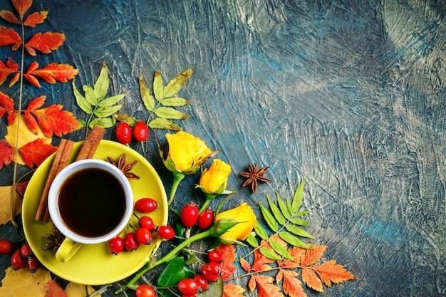 Fondo de otoño oscuro con taza de café y hojas de otoño.