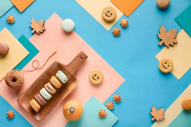 Fondo de otoño, papel geométrico plano con dulces y decoraciones de temporada.