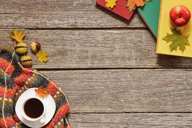 Fondo de otoño rojo, hojas verdes y amarillas, manzanas con una taza de café o té con libros