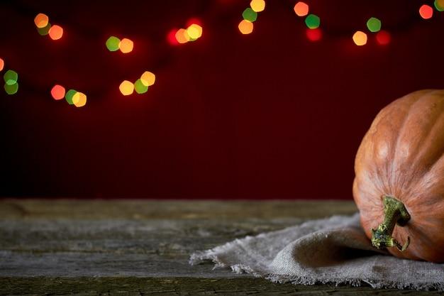 Fondo de otoño sobre una superficie de madera oscura, calabaza naranja sobre un fondo de luces borrosas