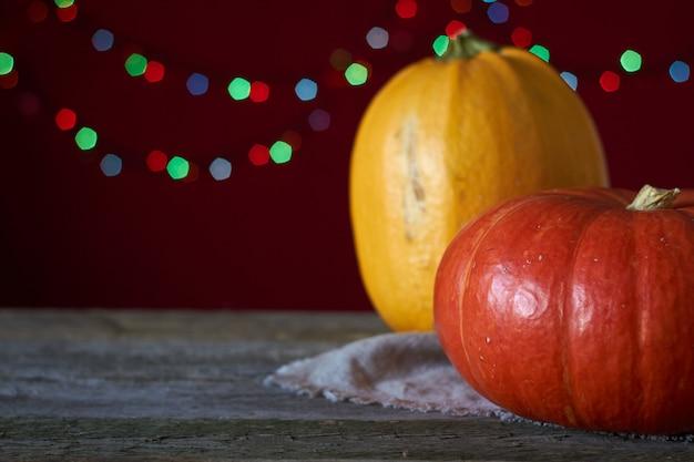 Fondo de otoño sobre una superficie de madera oscura, dos calabazas sobre un fondo de luces borrosas