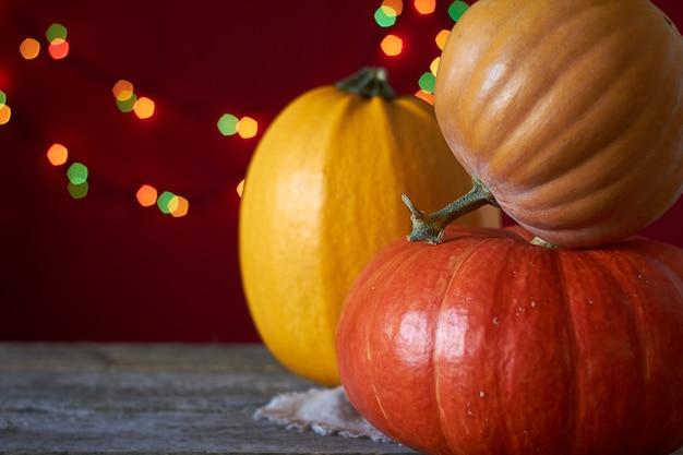 Fondo de otoño sobre una superficie de madera oscura, tres calabazas sobre un fondo de luces borrosas