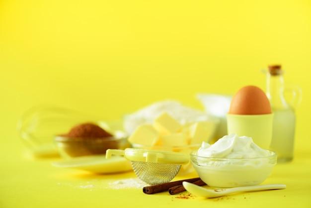 Fondo de panadería de vacaciones. estructura de los alimentos: mantequilla, azúcar, harina, leche, huevos, aceite, cuchara, rodillo, cepillo, batidor, canela sobre fondo amarillo.